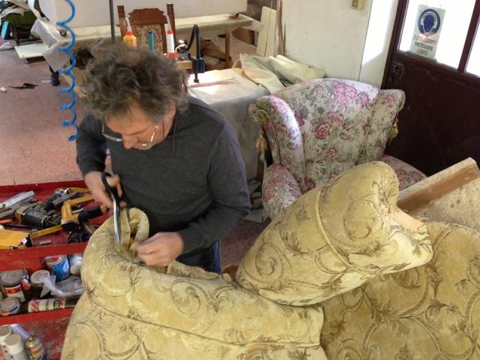 Un artigiano che rinnova una poltrona